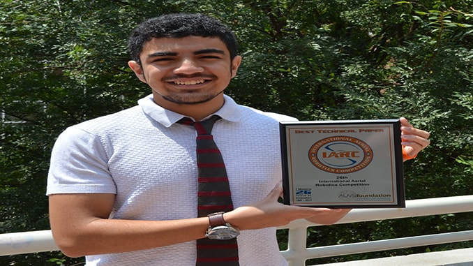NDSU Computer Science student Abdullah Almosalami shows off the award received by the team at the International Aerial Robotics Competition.