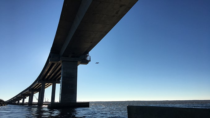 The N.C. Department of Transportation has another new tool to help make our roadways safer: Drones. This week, the Marc Basnight Bridge over Oregon Inlet became the first bridge in the state inspected using a drone as part of the regular biennial inspection process. Inspection crews monitored live high-definition video feeds from the drone as it was flown around the bridge's 10 largest columns, looking for any potential defects that would require further action. NCDOT will use drones to conduct bridge inspections faster, saving money and reducing the need for lane closures. Drones will not replace a traditional visual inspection in most instances. However, they will be used to supplement traditional inspections and add great benefit by being able to inspect areas of the bridge that are difficult to reach during a traditional visual inspection. A waiver granted to NCDOT in 2020 by the Federal Aviation Administration allows the department to operate drones beyond visual line of sight (BVLOS) when inspecting bridges. This lets the operator fly the drone around pillars, between girders, and even inside columns. The drone used in this case, a Skydio 2, is equipped with detect-and-avoid technology that allows it to operate within a foot of the bridge structure without risk of crash.